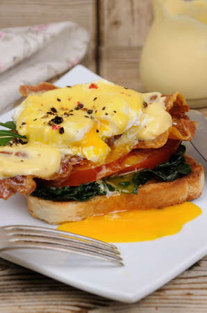 Eggs Benedict with tomato, slices of bacon, spinach under hollandaise sauce on toast Stock Photo - 82186669