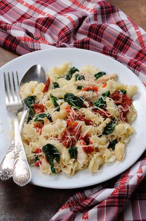 Warme salade pasta met kip, zongedroogde tomaten, spinazie, peper en gearomatiseerde Parmezaanse kaas Stockfoto