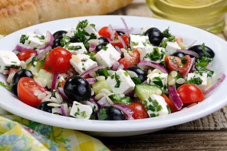 greek salad orzo pasta with black olive, red onion and cucumber, cherry tomatoes, feta and herbs. Horizontal shot. foreground Stock Photo
