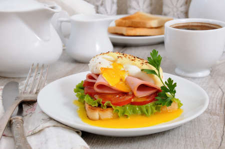 Toast with slices of ham and tomatoes, Benedict egg with Dutch sauce for Breakfast