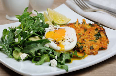 Brunch Idea. Egg poached with pumpkin spinach pancakes and garnish from arugula, avocado, mint leaves, and ricotta