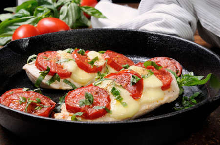 Langet from chicken breast with tomato and mozzarella. A-la caprese. Archivio Fotografico