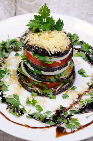 Appetizer from eggplant , slices of mozzarella combined in a pile with tomatoes spilled with herbs, seasoned   Parmesan cheese Stock Photo