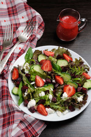 Salad of vinaigrette with strawberries, tender feta and strawberry sauce. Vertical shot.