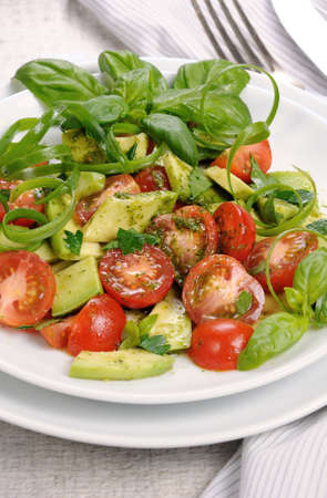 Delicate slices of avocado with tomatoes, dressed   pesto sauce.