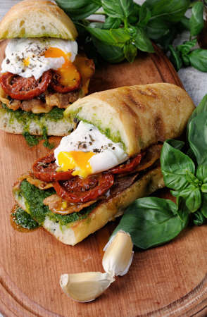 Toasted ciabatta with pesto, slices of bacon, sun-dried tomatoes and poached egg