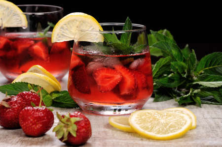 oneself: A glass of chilled strawberry lemonade, mint leaves, a slice of lemon with ice
