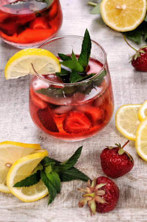 A glass of chilled strawberry lemonade, mint leaves, a slice of lemon with ice