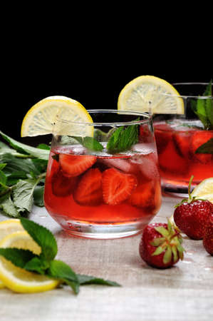 A glass of chilled strawberry lemonade, mint leaves, a slice of lemon with ice Stock Photo - 84079367