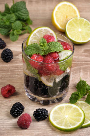 A glass of lemonade from the berries of blackberry and raspberry with lime and mint Stock Photo
