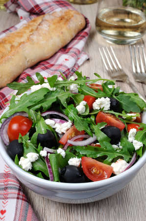 oneself: Variation of Greek salad with arugula, cherry slices, feta and olives