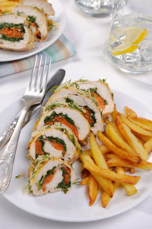 Roll from chicken breast with spinach and carrots under a crust of parmesan, dill, garnish of french fries Stock Photo