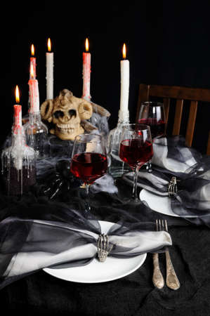 Napkin with a clip in the form of a skeleton of a brush as an element of a decor of a holiday table for Halloween