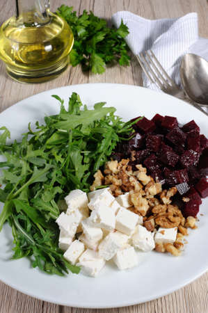 Ingredients for the preparation of salad from roasted beets, arugula, cheese feta, and walnuts. Vertical shot. View from above.