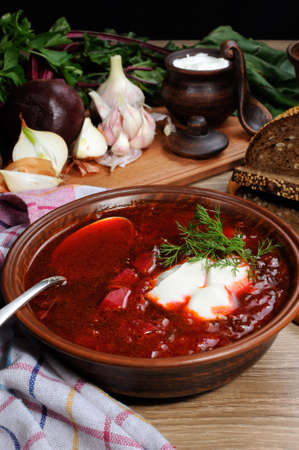 Borscht-vegetable beetroot soup, on the table with slices of rye cereal bread and gluten of sour cream, garlic and herbs. Rustic style.