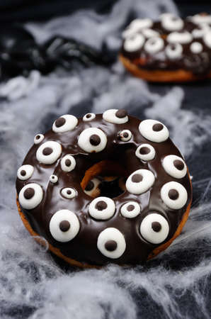 Donuts with chocolate icing decorated googly eyes on Halloween Stock Photo