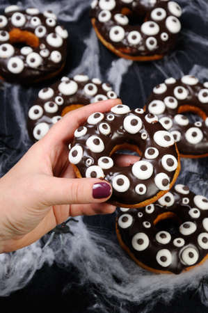 oneself: Hand holds a donut with chocolate icing decorated googly eyes on Halloween Stock Photo
