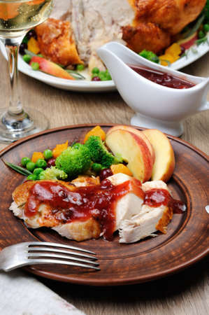 Slices of baked turkey with cranberry-orange sauce with fruit and vegetable garnish