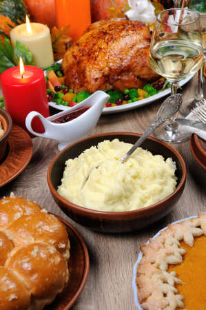 A bowl of mashed potatoes on a table among the pumpkin pie, baked turkey, cranberry-orange sauce,   a glass of white wine for Thanksgiving Stock Photo - 88251962