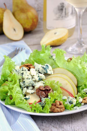 A light lettuce salad with pear slices, gorgonzola pieces and walnut seasoned with olive oil