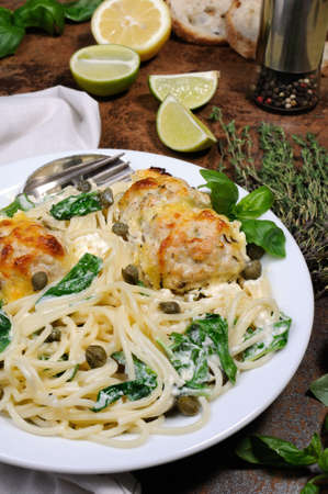 Spaghetti with chicken meatballs in cheese cream sauce , spinach and capers Stock Photo