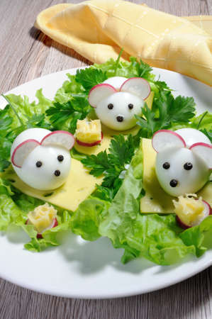 Serving a festive childrens snack, boiled eggs in the form of mice in lettuce leaves and cheese cubes Stock Photo