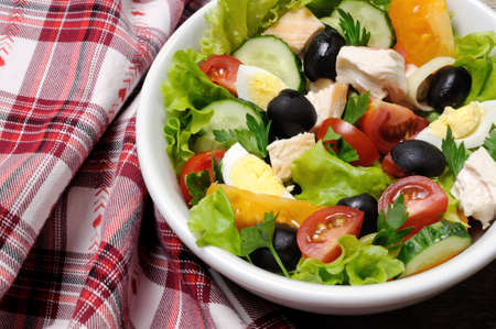 Vegetable salad with chicken and eggs, olives in lettuce leaves. Horizontal shot.