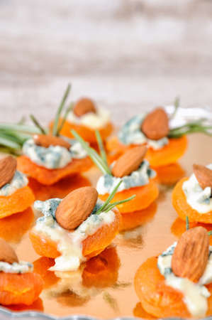 Cocktail snack from dried apricots with gorgonzola and almonds Stock Photo - 90420884