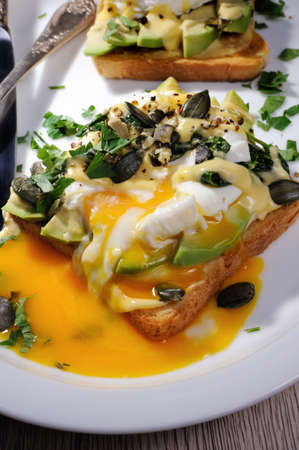 Eggs Benedict on toast with Dutch sauce, slices of avocado