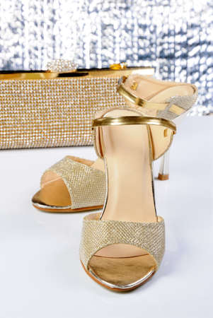 A pair of gold sandals with a high heel, with a golden clutch on the table