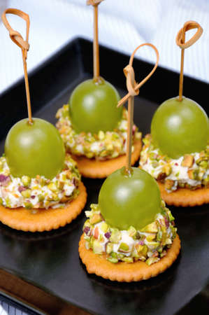 Canape  of cottage cheese cushions  in pistachios with grapes on cracker