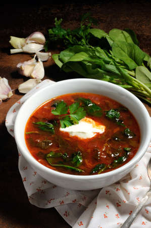Vegetable bowl, tomato soup with spinach and sour cream. Vertical shot.