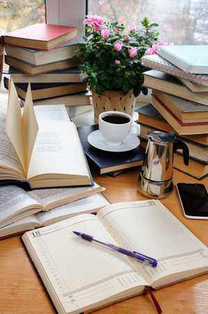 Textbooks, notepad and pen with a cup of black coffee with a coffee pot on a wooden table. Education concept. Stock Photo