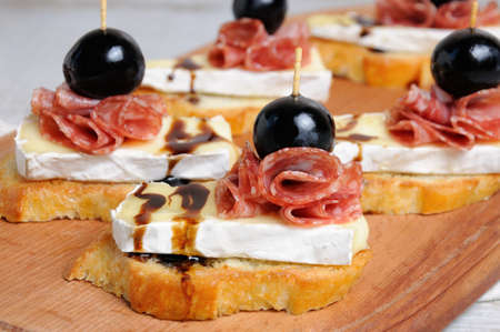 Snack from a toasted slice of baguette with soft under a noble white mold Cheese Brie, salami, a berry of grapes with honey