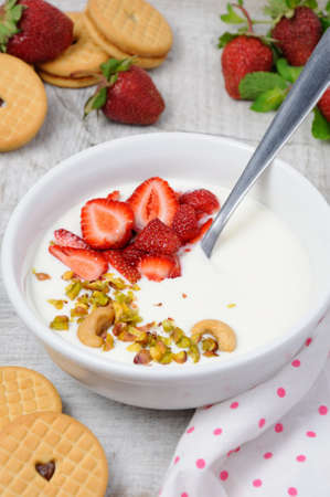 Chilled Buttermilk soup from Greek yogurt with strawberries and pistachios, cashews. Serve with crispy biscuits. Vertical shot.