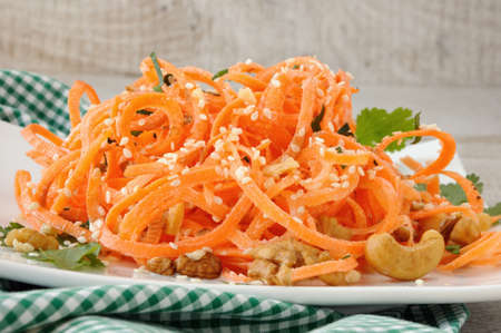 Carrot ribbon salad bathed with yoghurt dressing seasoned with fried nuts and sesame seeds, fresh coriander