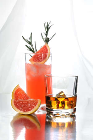 Paloma cocktail in Collins Glass, from tequila with grapefruit juice, decorated with a slice of grapefruit and rosemary.Whiskey in rocks glass with  ice cubes . Drinks  on a light background.