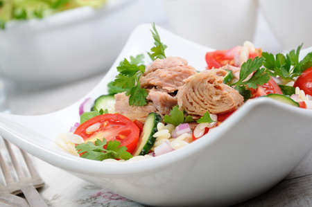 Salad from canned tuna with tomatoes, cucumber and orzo