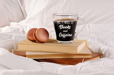 Morning cup of coffee with chocolate cakes Macaroons, on a pile of books in bed. All I need is books and caffeine.