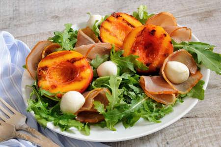 Salad with dried ham, grilled nectarine, mozzarella and arugula Banco de Imagens
