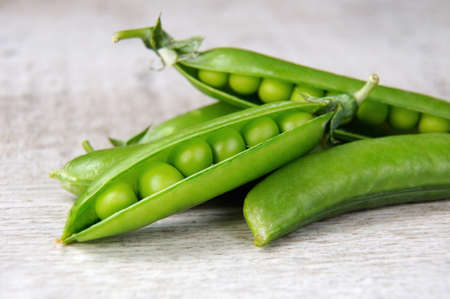 Pods of fresh green peas on a wooden background closeup Stock Photo