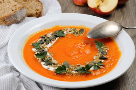 A wipe of pumpkin-apple soup with a tender, soft consistence,  yoghurt  and seasoned with pumpkin seeds and sunflower seeds. This is what you need for those who watch their health. Фото со стока