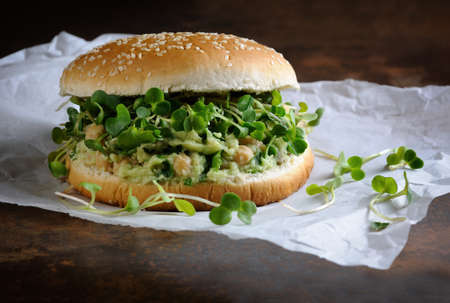 A vegetarian burger made from a gluten-free bun with chickpeas, avocado and herbs, radish sprouts. A quick and healthy lunch idea that you feel energized throughout the day. Stock Photo