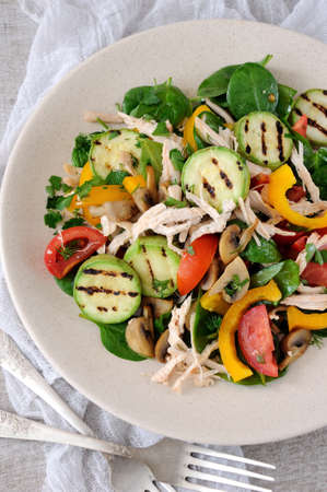 Warm chicken salad with spinach, tomato slices, sweet pepper, grilled zucchini, and champignons, all dressed with herbs and fragrant oil.