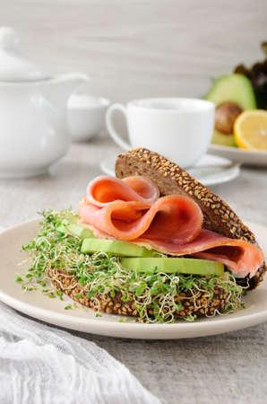 Panino di pane di segale con cereali, fette di prosciutto e avocado con germogli di erba medica germogliata.