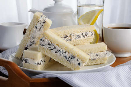 Slices of sandwich with ricotta and black olives on a plate, for breakfast with a cup of coffee