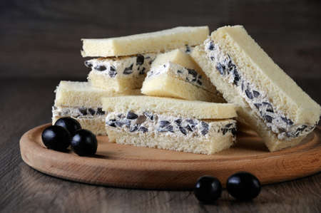 Slices of sandwich with ricotta and black olives