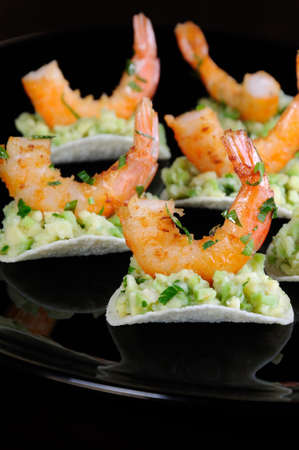 light snack of crisps with avocado filling and fried shrimp flavored with herbs. Stock Photo - 105143785