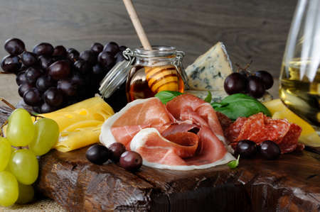 Antipasto catering platter with jerky bacon,  prosciutto, salami, cheese,   and olives and grapes on a wooden background