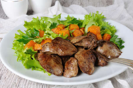 Fried chicken liver with vegetable garnish, baked pumpkin in lettuce leaves Фото со стока